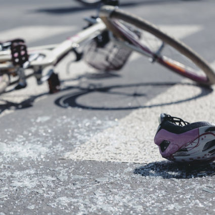 Helmet and bicycle on pedestrian crossing after traffic accident