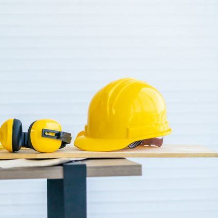 Yellow wood working tool with headphone ear protection on a table