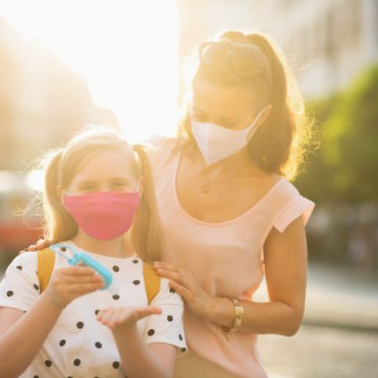 mother and school child disinfecting hands outdoors
